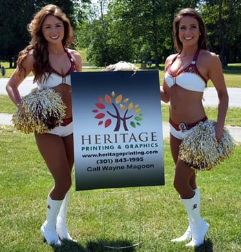 Redskin Cheerleaders with a Heritage Printing Outdoor Sign